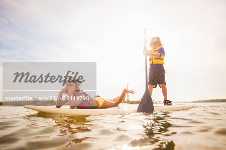 Boy standup paddleboarding with sister in the sound, Fort Walton, Florida, USA Stock Photo - Premium Royalty-Free, Image code: 614-08119790
