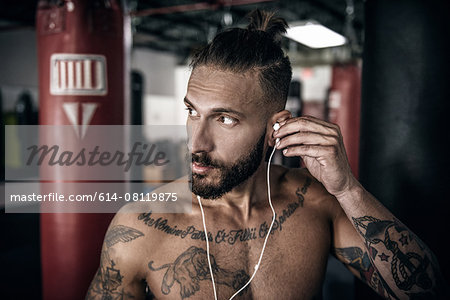 Male boxer inserting ear phones in preparation for training Stock Photo - Premium Royalty-Free, Image code: 614-08119875