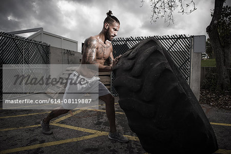 Male boxer training with truck tyre in yard Stock Photo - Premium Royalty-Free, Image code: 614-08119887