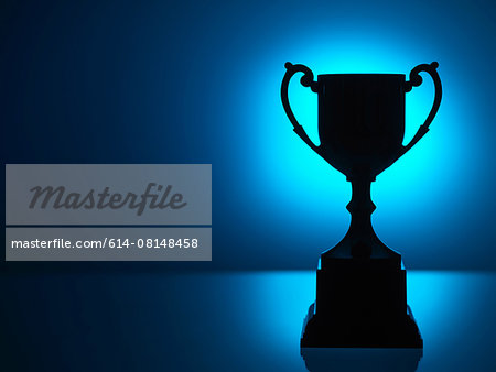 Silhouetted trophy with blue background Stock Photo - Premium Royalty-Free, Image code: 614-08148458