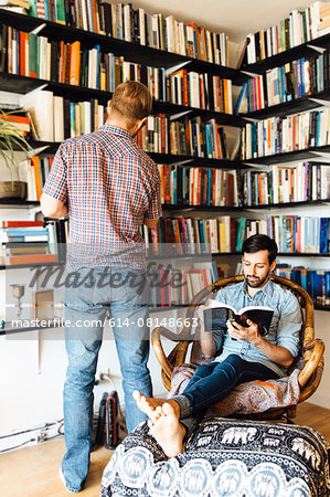 Male couple at home, reading and looking at books on bookshelf Stock Photo - Premium Royalty-Free, Image code: 614-08148663