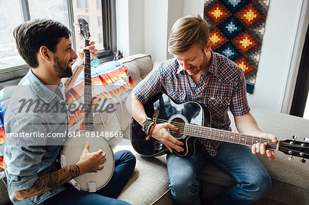 Male couple at home, play guitar and banjo, laughing Stock Photo - Premium Royalty-Free, Image code: 614-08148666