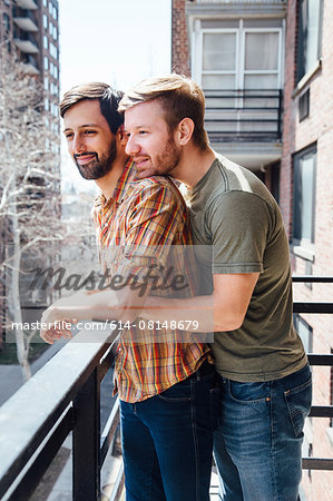 Male couple standing on balcony, looking at view, embracing Stock Photo - Premium Royalty-Free, Image code: 614-08148679