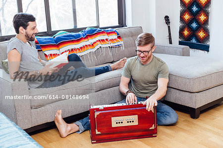 Male couple at home, Young man on sofa watching his partner play musical instrument Stock Photo - Premium Royalty-Free, Image code: 614-08148694