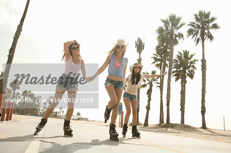 Three young women, holding hands, inline skating Stock Photo - Premium Royalty-Free, Image code: 614-08201900