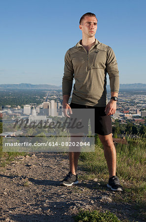 Portrait of young male runner on dirt track above city in valley Stock Photo - Premium Royalty-Free, Image code: 614-08202044