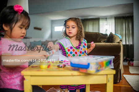Two young girls sitting at table, making art, using paint Stock Photo - Premium Royalty-Free, Image code: 614-08219822