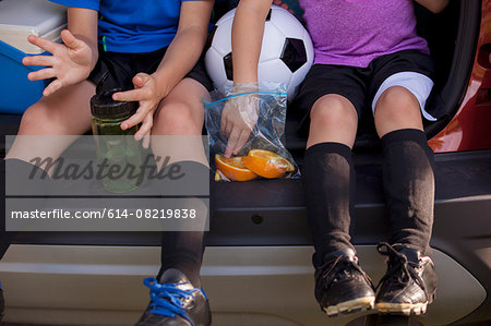 Waist down of boy and younger sister sitting in car boot eating oranges on football practice break Stock Photo - Premium Royalty-Free, Image code: 614-08219838