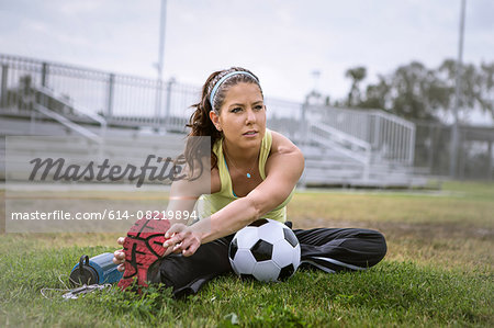 Soccer player stretching in field Stock Photo - Premium Royalty-Free, Image code: 614-08219894