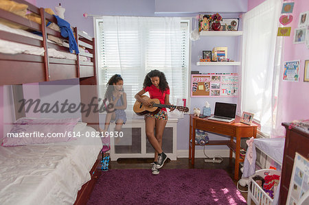 Girls sitting on bedroom windowsill singing and playing guitar Stock Photo - Premium Royalty-Free, Image code: 614-08219930