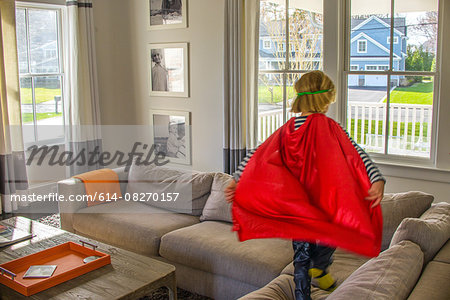 Boy with red cape playing on sofa Stock Photo - Premium Royalty-Free, Image code: 614-08270157