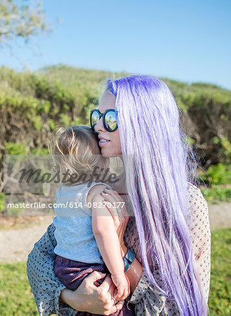 Young woman with long purple hair,  holding baby daughter Stock Photo - Premium Royalty-Free, Image code: 614-08270177