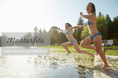 Girls in bikini jumping into lake, Seattle, Washington, USA Stock Photo - Premium Royalty-Free, Image code: 614-08270202