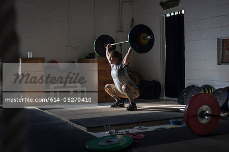 Crossfitter lifting barbell in gym Stock Photo - Premium Royalty-Free, Image code: 614-08270410