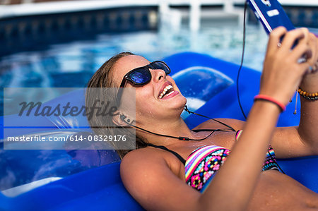 Teenager using smartphone on inflatable in swimming pool Stock Photo - Premium Royalty-Free, Image code: 614-08329176