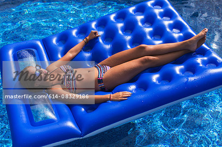 Teenager relaxing on inflatable in swimming pool Stock Photo - Premium Royalty-Free, Image code: 614-08329186
