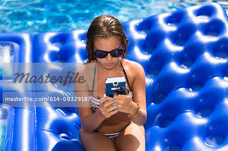 Teenager using smartphone on inflatable in swimming pool Stock Photo - Premium Royalty-Free, Image code: 614-08329187