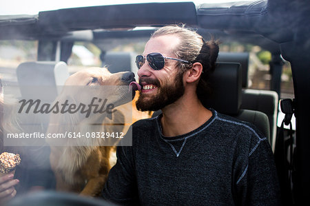 Dog licking young mans bearded face in jeep Stock Photo - Premium Royalty-Free, Image code: 614-08329412