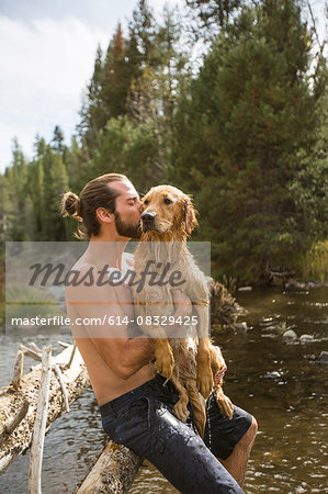 Young man kissing his wet dog at river, Lake Tahoe, Nevada, USA Stock Photo - Premium Royalty-Free, Image code: 614-08329425