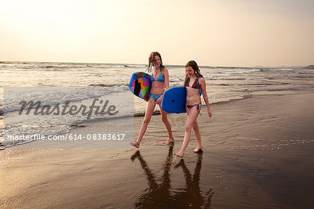 Teenage girl and sister carrying surfboards on beach, Goa, India Stock Photo - Premium Royalty-Free, Image code: 614-08383617
