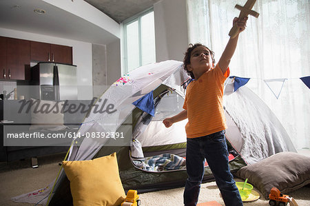 Young boy in living room using tent as den, arm raised, looking up, holding sword Stock Photo - Premium Royalty-Free, Image code: 614-08392391