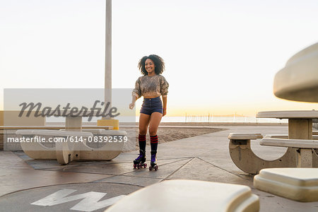 Mid adult woman on rollerskates, near beach Stock Photo - Premium Royalty-Free, Image code: 614-08392539