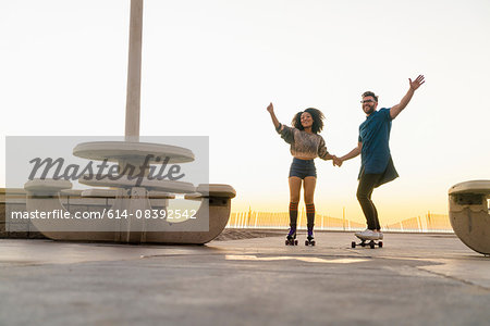 Couple using rollerskates and skateboard, holding hands, smiling Stock Photo - Premium Royalty-Free, Image code: 614-08392542