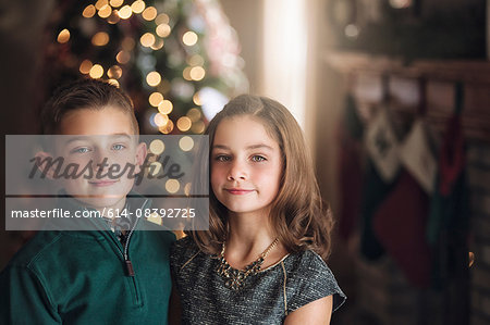 Portrait of girl and boy in front of christmas tree looking at camera smiling Stock Photo - Premium Royalty-Free, Image code: 614-08392725