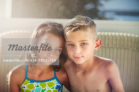 Portrait of boy and girl arms around each other looking at camera smiling Stock Photo - Premium Royalty-Free, Image code: 614-08535989