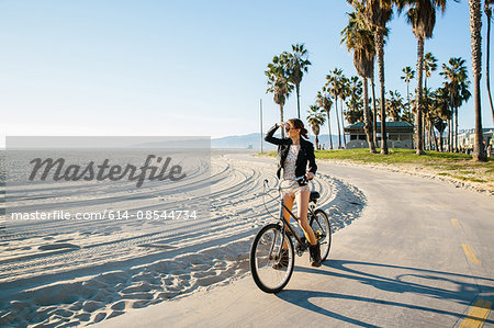 Young woman cycling at beach looking out to sea, Venice Beach, California, USA Stock Photo - Premium Royalty-Free, Image code: 614-08544734