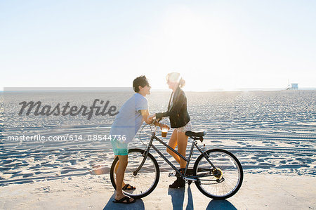 Young couple with bicycle chatting on sunlit beach, Venice Beach, California, USA Stock Photo - Premium Royalty-Free, Image code: 614-08544736