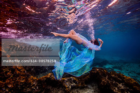 Woman underwater in ocean over coral reef Stock Photo - Premium Royalty-Free, Image code: 614-08578258
