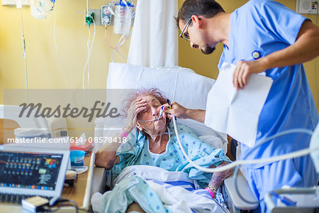 Hospital staff checking on patient on hospital bed Stock Photo - Premium Royalty-Free, Image code: 614-08578418