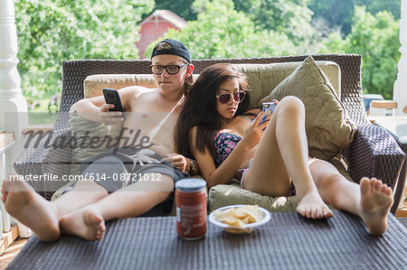Teenage couple wearing bikini and swim shorts reclining on patio sofa reading smartphones Stock Photo - Premium Royalty-Free, Image code: 614-08721012