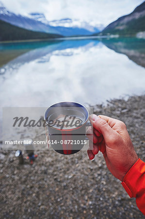 Cropped view of mans hand holding cup of tea by river, Banff, Alberta, Canada Stock Photo - Premium Royalty-Free, Image code: 614-08721015