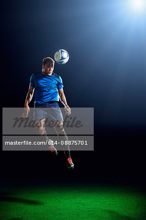 Male soccer player heading ball