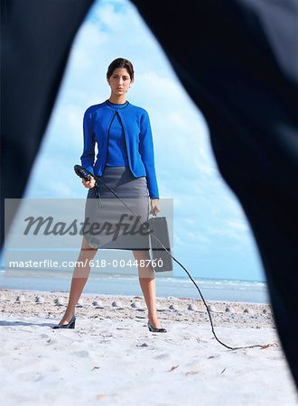 portrait of a business woman carrying a briefcase and holding a whip