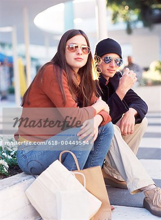 portrait of a young couple with shopping bags resting Stock Photo - Premium Royalty-Free, Image code: 618-00449584