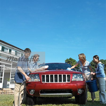 portrait of mother and father with son and daughter washing the car together Stock Photo - Premium Royalty-Free, Image code: 618-00459191