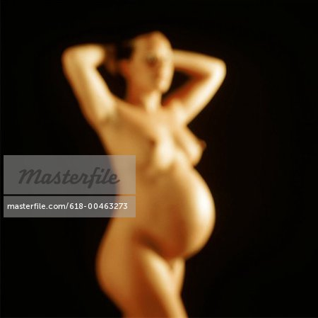 blurred shot of a nude pregnant woman standing with her hands behind her head Stock Photo - Premium Royalty-Free, Image code: 618-00463273