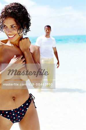 view of a young woman standing topless on the beach with young man in background Stock Photo - Premium Royalty-Free, Image code: 618-00463990