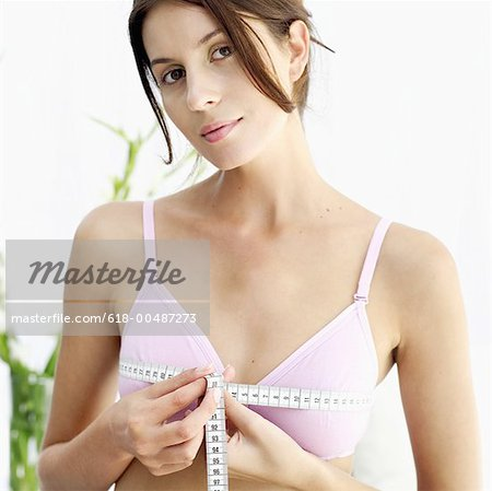 Young woman measuring her bust wearing lingerie Stock Photo - Premium Royalty-Free, Image code: 618-00487273