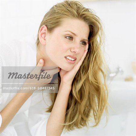 close-up of a young woman with her hands on her neck Stock Photo - Premium Royalty-Free, Image code: 618-00487345