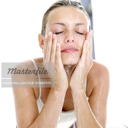 portrait of a woman washing her face with water Stock Photo - Premium Royalty-Free, Image code: 618-00489331