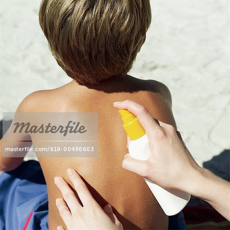 rear view of a young boy getting his back sprayed with sunscreen lotion Stock Photo - Premium Royalty-Free, Image code: 618-00490603