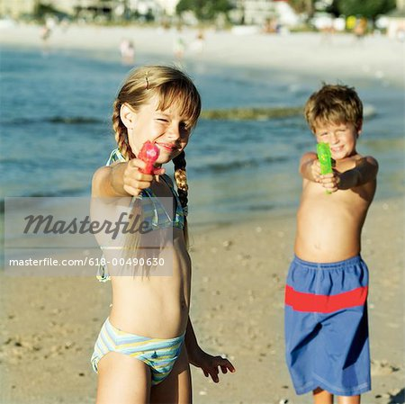 brother and sister playing with water pistols on the beach
