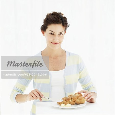 Portrait of a young woman applying butter on bread Stock Photo - Premium Royalty-Free, Image code: 618-00491006
