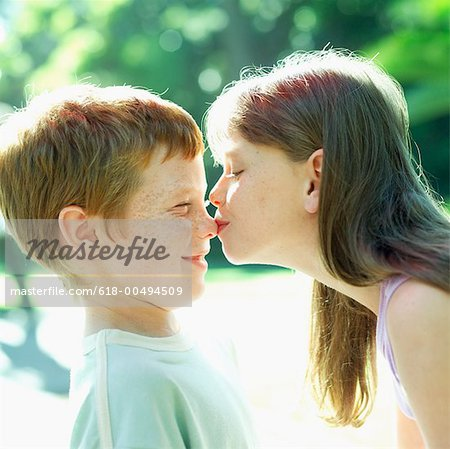 Young girl kissing a young boy (8 11) on his nose Stock Photo - Premium Royalty-Free, Image code: 618-00494509