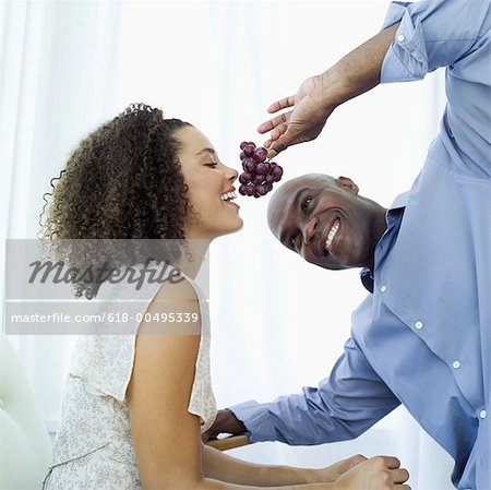 Young man feeding a Young woman a bunch of grapes Stock Photo - Premium Royalty-Free, Image code: 618-00495339