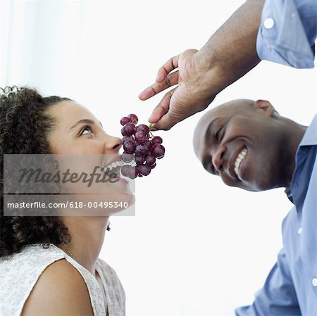 Young man feeding a Young woman a bunch of grapes Stock Photo - Premium Royalty-Free, Image code: 618-00495340